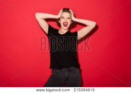 Happy punk woman screaming and holding her head while looking at the camera over red background