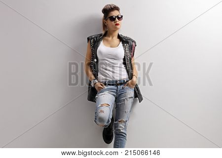 Punk girl with a pair of sunglasses leaning against a wall