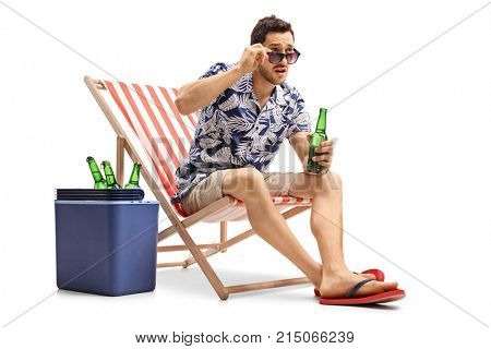 Astonished tourist with a beer bottle sitting in a deck chair and staring over his sunglasses isolated on white background