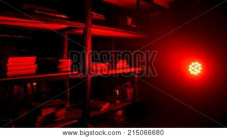 Pantry or storeroom with red lamp and light. Red light bulb glowing from fixture in dark room. Red Vintage Room Background
