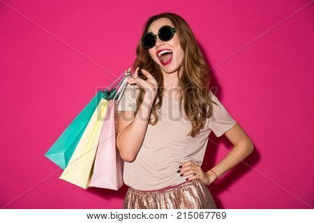 Photo of cheerful young lady standing isolated over pink background holding shopping bags. Looking camera.