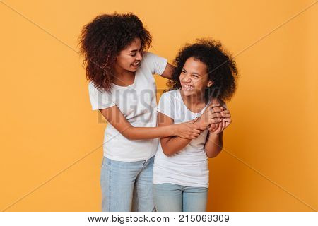 Two happy afro american sisters having fun while standing isolated over orange background