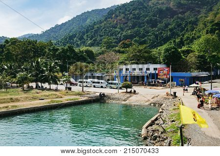 Koh Chang, Thailand - December 20, 2015: Port ferry boat with concrete ferry pier. The arrival of the ferry. A taxi waits for tourists to take them to different places around the island