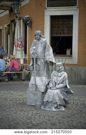 DUSSELDORF, GERMANY, JUN.13, 2010: Street silver alive statues sculptures of king and queen. European street living sculptures. Silver painted sculpture artists. Street living sculptures scene
