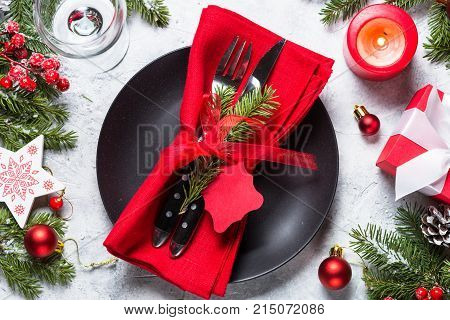 Christmas table setting - plate cutlery wineglass candle with christmas decorations over gray stone table. Top view.