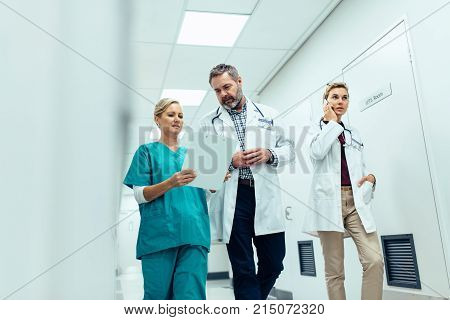 Doctors team walking in hospital corridor indoors. Emergency paramedic team in hospital hallway.
