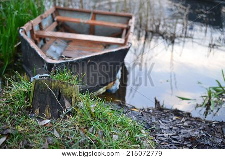 A dilapidated boat moored on the river bank by an iron chain