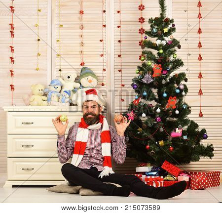 Man With Beard In Hat And Scarf Holds Christmas Balls.