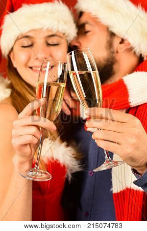 Mister And Missis Claus Hold Glasses Of Champagne Cuddling