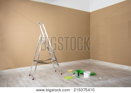 Freshly Painted Room With Ladder And Painting Equipments At Home