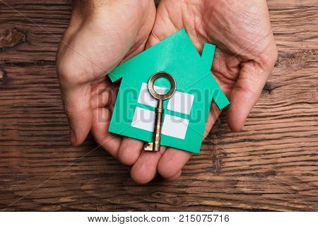 High Angle View Of Hands Holding Paper House With House Key Against Wooden Table