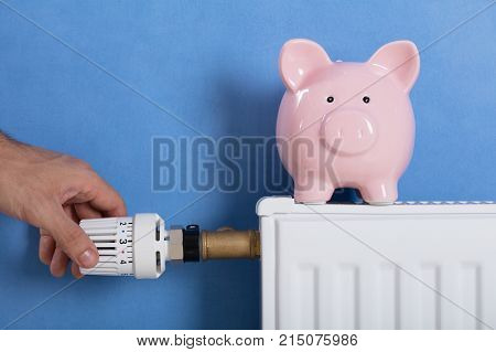 Close-up Of Man's Hand Adjusting Thermostat With Piggy Bank On Radiator