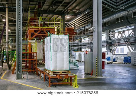 Bags with chemical production on conveyor at packing area at chemical factory.