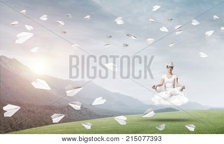 Young woman keeping eyes closed and looking concentrated while meditating on cloud among flying paper planes with beautiful and breathtaking landscape on background.