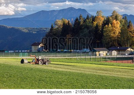 OBERMILLSTATT/ AUSTRIA - OCTOBER 8, 2017. Tractor hay bale wrapper, picking up and applying plastic cling wrap to a round bale. Village Obermillstatt, Gurktal Alps, Carinthia, Austria