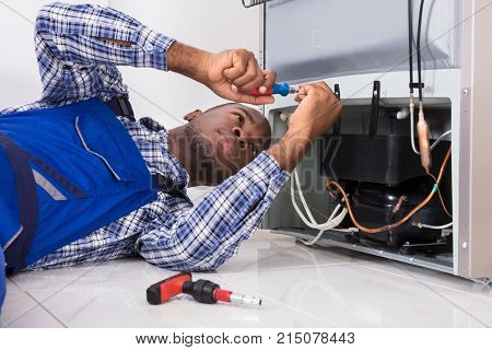 Young Male Serviceman Working On Fridge With Screwdriver At Home
