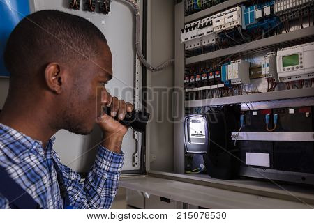 Close-up Of A Electrician Examining A Electric Meter With A Torch