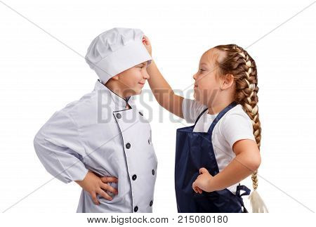 Girl assistant in apron adjusting the cap small cook with bark holding hands in the sides on white isolated background