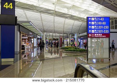 CHEK LAP KOK, HONG KONG - OCT 19, 2017: Passengers make their way past the retail shops towards their departure gate in Chek Lap Kok airport