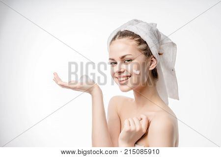 happy young girl with white towel on head cleanses facial skin with foam, smiling