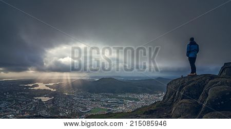 Unidentifiable tourist standing on the top of mount Ulriken in Bergen and looking at the landscape below, Norway