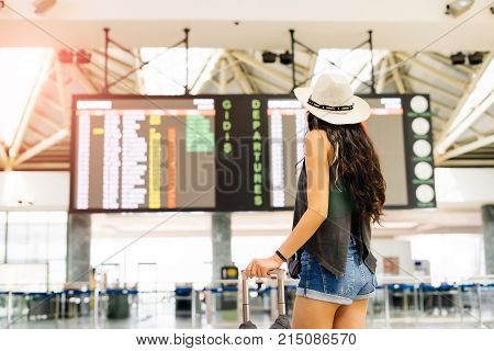 Young woman in international airport looking at the flight information board, checking her flight.Departures and arrivals board.Unrecognizable