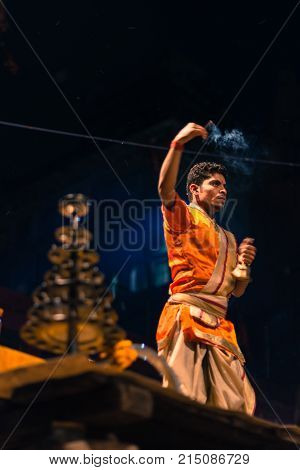 VARANASI INDIA - MARCH 14 2016: Vertical picture of unidentified Hindu indian man praying at religious Ganga Aarti ritual at Dashashwamedh Ghat in Varanasi India.
