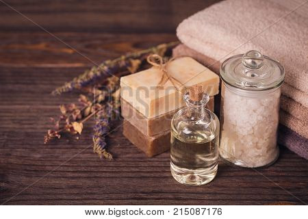 Spa products for facial and body care. Natural sea salt homemade soap massage oil and colorful towels. Spa and bodycare concept. poster