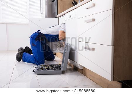Plumber In Overall Fixing Sink Pipe In Kitchen