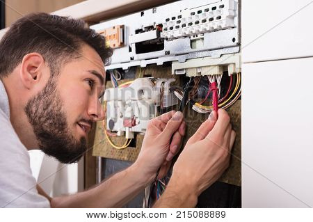 Male Technician Examining Dishwasher With Digital Multimeter