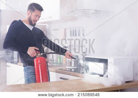 Young Man Spraying Fire Extinguisher On Microwave Oven In The Kitchen