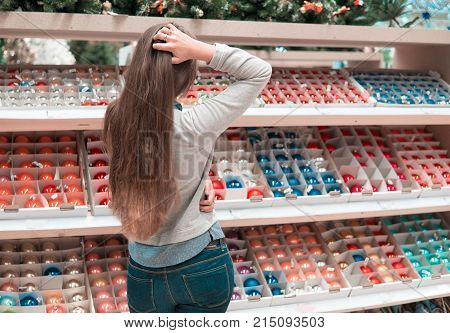 Cheerful happy customer girl choosing gifts for Christmas and New Year. She is taking red Christmas tree decoration balls. difficult decision. Various choice