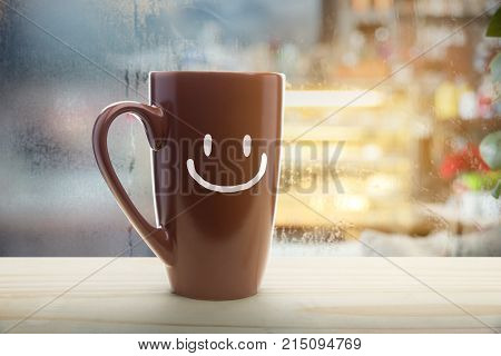 Brown mug of coffee with a happy smile Steaming red coffee cup on a rainy day window background Good morning or have a happy day message concept