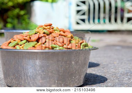 Dry dog food in in the stainless steel bowl and water