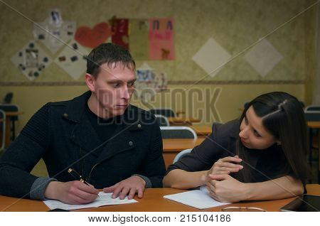 Two students sit at a desk and write an examination work. The male student looks on female student notebook and tries to write off the exam work but the student girl closes the notebook with her hand.