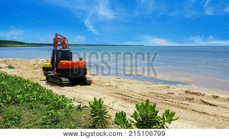Excavator or digger moving beach sand after erosion by the tides on a tropical beach with calm ocean in Cairns Queensland Australia