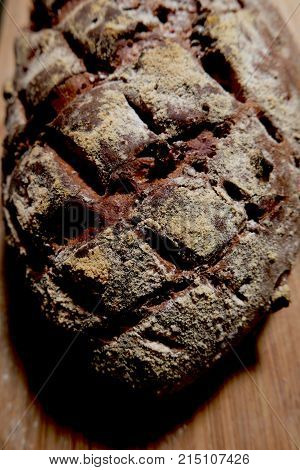A craggy cross hatched loaf of artisanal walnut bread dusted with flour the deep furrows of slash marks in dark shadows.