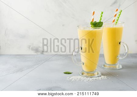 Pumpkin smoothies with ginger and coconut shavings and mint in a glass on light stone or concrete background. Healthy and delicious drink for breakfast. Selective focus. Top view. Copy space.