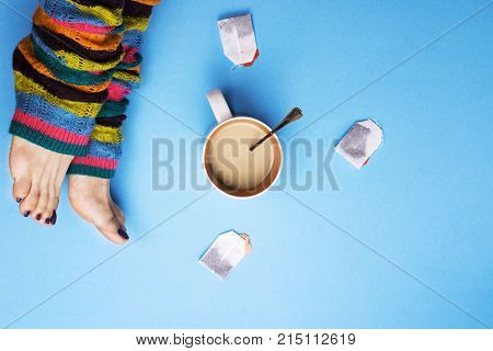 Girl in socks and surrounded by coffee and tea. The concept of stopping for coffee breaks. Drinks.