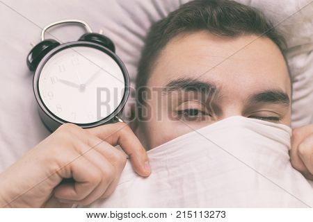 Young man sleeping in bed in the morning and can't Wake up