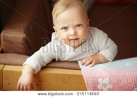 Innocent infant sits on the sofa and holds relying on support.t. Adorable newborn child in white sweatshirt