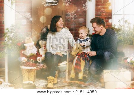 Young Happy Parents With Little Child Boy On Rocking Horse, In Decorated New Year Room With Santa At