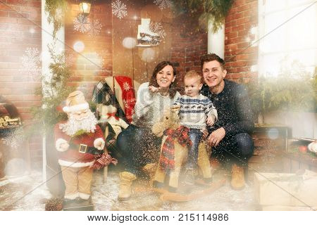 Young Happy Parents With Cute Little Child Boy On Rocking Horse In Decorated New Year Room With Sant