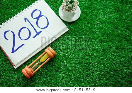 Happy New Year Background With Hourglass, Plants And Notebook Has New Year Message 2018 Isolated Pla