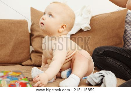 Profile of innocent infant with perfect skin stands on arms and legs on sofa with broad smile. Adorable newborn child in pants