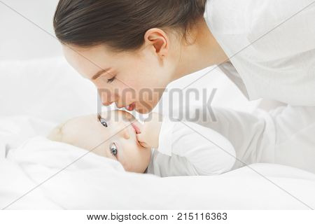 Mother kisses the baby lying. the child looks in the frame. The warm relationship between a child and mother