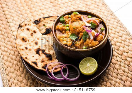 Aloo Gobi matar is a famous Indian curry dish with potatoes and cauliflower and green peas, selective focus