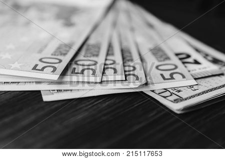 Euro banknotes on the wood rustic table. Black and white photo