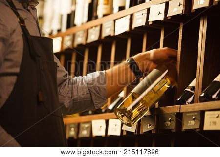 Expert in winemaking choose elite white wine in cellar. Males hand on background of shelves with wine, sommelier at work