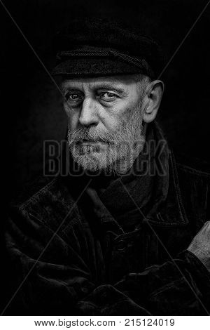 Portrait of a mature man with a white beard and a cap on the head. He could be a sailor a worker a docker or even a gangster or a thug. He has a penetrating gaze.